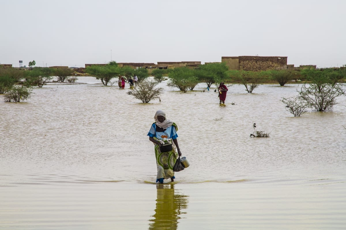 A woman wades through a submerged field after floods brought by the strong rain, took place in Khartoum, Sudan 3 August 2020 [Mahmoud Hjaj/Anadolu Agency]