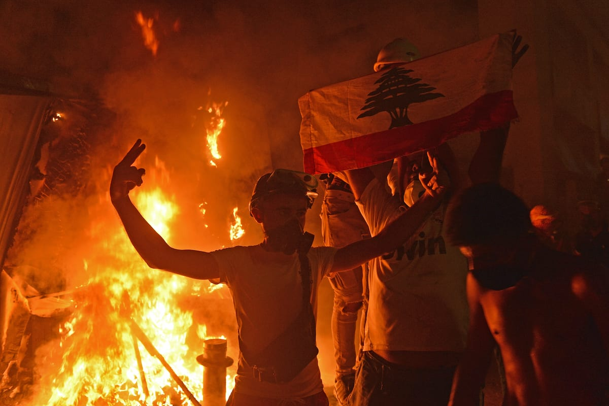 Lebanese demonstrators try to break through a barrier as they set on fire amid clashes with security forces in the vicinity of the parliament building following resignation of Lebanese government, during the fourth day of the demonstration after a fire at a warehouse with explosives at the Port of Beirut led to massive blasts on 4th August in Beirut, Lebanon on 11 August 2020. [Houssam Shbaro - Anadolu Agency]