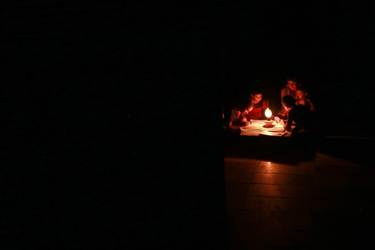 Children study under candle light during a power cut in Khan Yunis, Gaza on August 18, 2020 [Mustafa Hassona/Anadolu Agency]