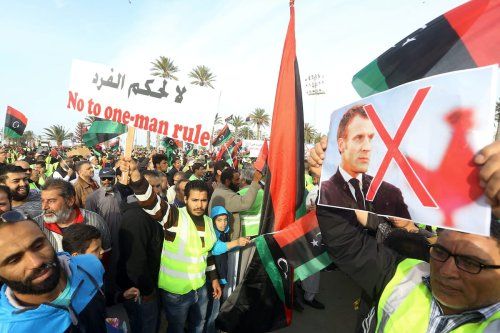 """Libyans wave the national flag and carry a portrait of French President Emmanuel Macron during a demonstration with yellow vests (""""gilets jaunes"""") against strongman Khalifa Haftar in the capital Tripoli's Martyrs Square on 19 April 2019. [MAHMUD TURKIA/AFP via Getty Images]"""