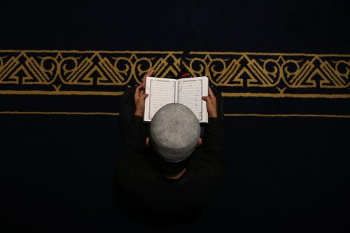 A Muslim believer reads Koran before breaking his fast at the Al-Azhar mosque on 12 May 2019, as they mark the 1079th anniversary of the establishment of the mosque, during the holy month of Ramadan in Egypt's capital Cairo. [MAHMOUD KHALED/AFP via Getty Images]