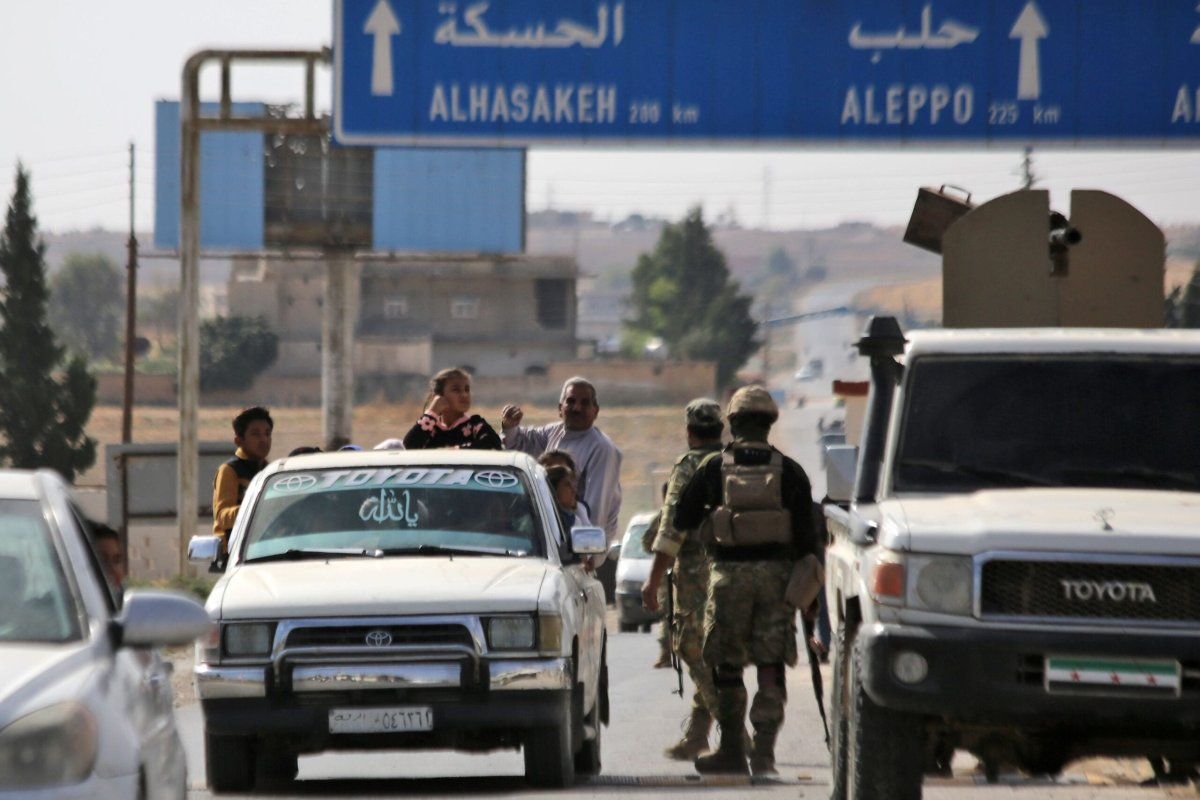 Turkish-backed Syrian fighters man a checkpoint in the town of Ayn al-Arus, south of the border town of Tal Abyad, on October 14, 2019 [BAKR ALKASEM/AFP via Getty Images]