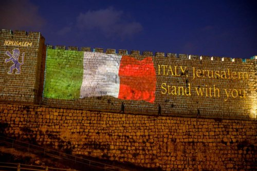 The Italian flag projected on the walls of the ramparts of Jerusalem's Old City in show of support for those suffering from coronavirus in Italy, on 15 March 2020 [MENAHEM KAHANA/AFP via Getty Images]