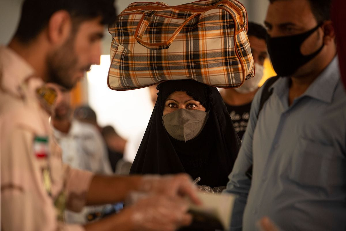 An Iraqi woman who had been stranded in Iran due to the novel coronavirus pandemic, looks on as a soldier questions a man, upon their arrival to Iraq via the Al-Shalamija border crossing, west of the southern city of Basra, on 27 May 2020. [HUSSEIN FALEH/AFP via Getty Images]