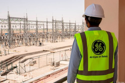 A mask-clad General Electric employee tours the Dhi Qar Combined Cycle Power Plant near the Iraqi city of Nasiriyah on June 16, 2020 [HUSSEIN FALEH/AFP via Getty Images]
