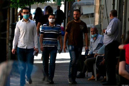 Mask-clad Palestinian men walk along a street in the occupied West Bank city of Ramallah, on July 13, 2020, amid the novel coronavirus pandemic crisis. [ABBAS MOMANI/AFP via Getty Images]