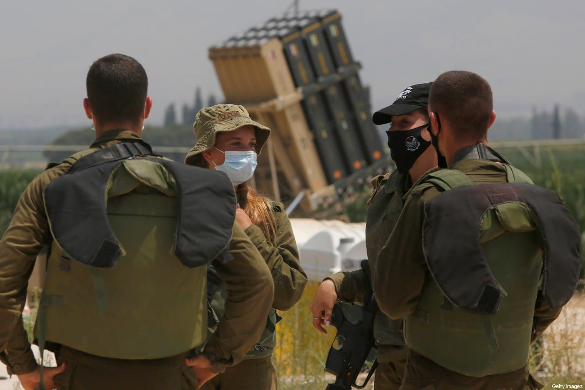 Israeli soldiers stand in front of an Iron Dome defence system battery in northern Israel near the border with Lebanon on 27 July 2020 [JALAA MAREY/AFP/Getty Images]