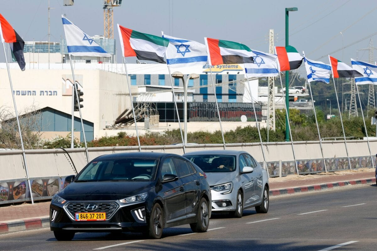 Cars pass by beneath Israeli and United Arab Emirates flags ligning a road in the Israeli coastal city of Netanya, on August 16, 2020 [JACK GUEZ/AFP via Getty Images]