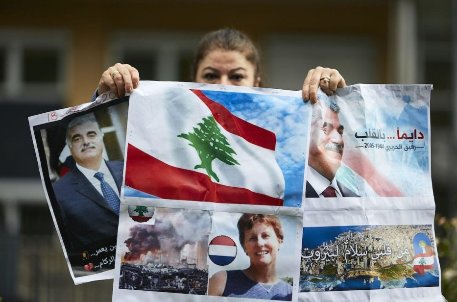 A supporter of former Prime Minister Rafiq Hariri holds posters outside the Lebanon Tribunal on 18 August 2020 in The Hague, Netherlands. [Pierre Crom/Getty Images]