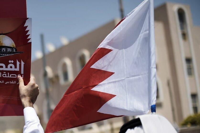 Bahraini men hold up a national flag [MOHAMMED AL-SHAIKH/AFP via Getty Images]