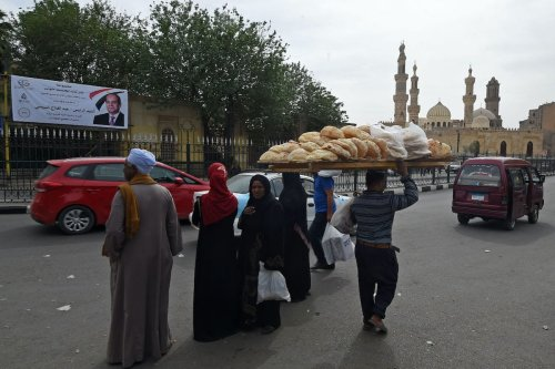 A bread seller walks in front of Al-Azhar Mosque in central Cairo on March 23, 2018. [FETHI BELAID/AFP via Getty Images]