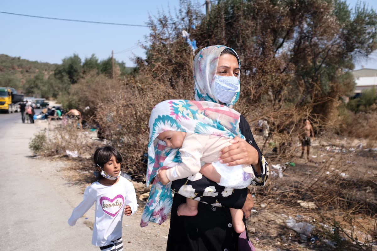 A woman walks with a little girl while carrying a baby on a roadside as many refugees and migrants remain homeless after a fire destroyed the Moria refugee camp on the Greek island of Lesbos, on 16 September 2020. [Aggelos Barai - Anadolu Agency]