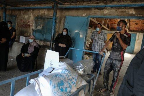 Palestinians receive food aid distributed by United Nations Relief and Works Agency for Palestine Refugees in the Near East (UNRWA) in Gaza City, Gaza on September 29, 2020 [Ali Jadallah/Anadolu Agency]