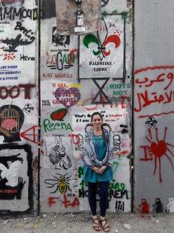 "Kadletz alongside part of the Israeli ""Separation Wall"" during her visit to Palestine in 2017 [Burna Kadletz/Middle East Monitor]"