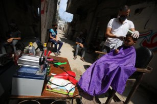 27-year-old Palestinian barber Sameh Alkassas moves his salon onto the street after authorities close shops as part of the lockdown to stop the spread of the coronavirus in Gaza on 14 September 2020 [Mohammed Asad/Middle East Monitor]