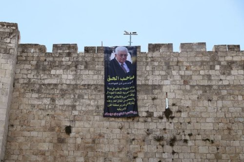 "Palestinian President Mahmoud Abbas is depicted on a banner hung on the walls of Jerusalem's Old City August 20, 2020. The writing in Arabic reads, ""The rightful owner Is stronger than all the capitals. We call upon the government of Abu Dhabi in the United Arab Emirates to revert to the inclusive Arab and Islamic position and to withdraw from the shameful agreement, and not to participate in making the American Deal of the Century pass. Jerusalem's wounds are not to be treated with the salt from your capitals."" [Ammar Awad/Twitter]"