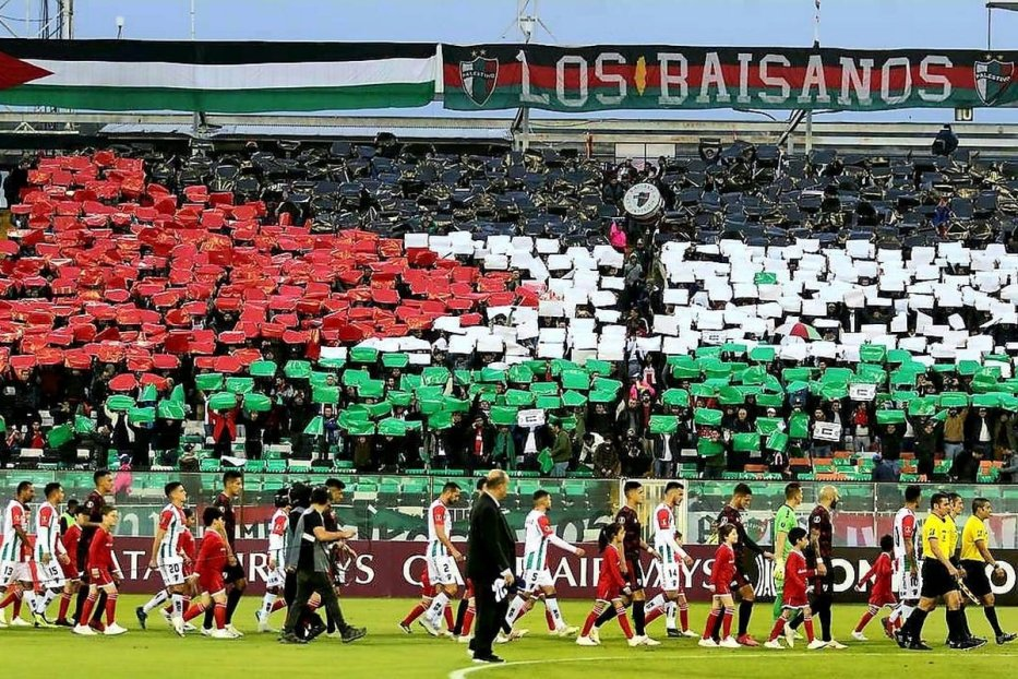 Fans carry cards to make the Palestinian flag at a football match in Chile, 22 September 2020