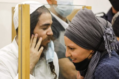 Amiram Ben-Uliel, a Jewish extremist convicted for the Duma arson murder speaks to his wife from behind a glass pane during a sentencing hearing at the central district court of Israel's central city of Lod on June 9, 2020 [MENAHEM KAHANA/AFP via Getty Images]