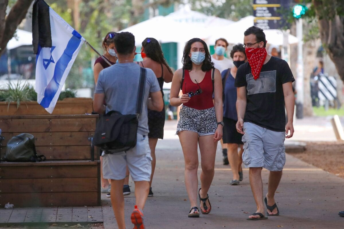 People, wearing protective masks due to the Covid-19 pandemic, walk in the Israeli coastal city of Tel Aviv on July 12, 2020 [JACK GUEZ/AFP via Getty Images]