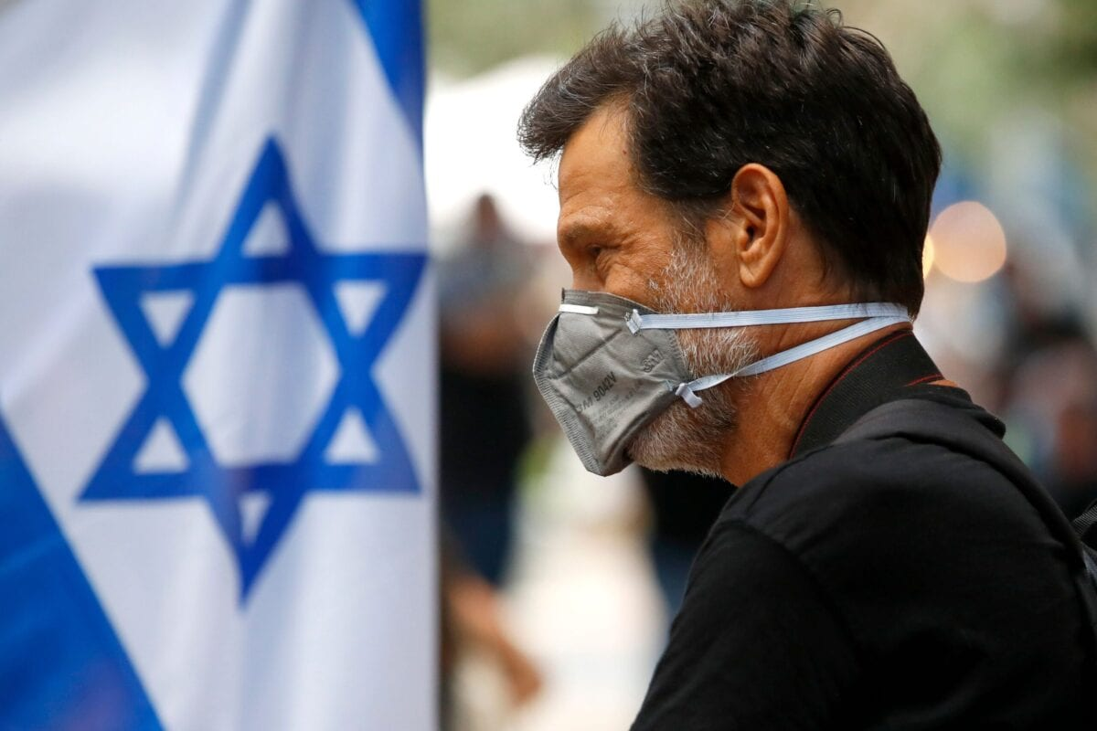 A man seen wearing a protective mask due to the Covid-19 pandemic, walks in the Israeli coastal city of Tel Aviv on July 12, 2020 [JACK GUEZ/AFP via Getty Images]