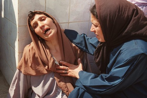 A distraught woman, who later was called the 'Madonna of Bentalha' is comforted by a relative at Zmirli hospital after having lost all her family on 23 September 1997 [HOCINE ZAOURAR/AFP via Getty Images]