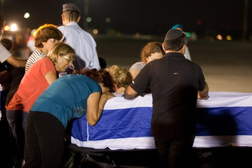 Relatives mourn over the coffin of one of the five Israelis who were killed during the terror attack on a tour bus in Burgas, Bulgaria, during a ceremony at the Ben Gurion International Airpor on July 20, 2012 near Tel Aviv, Israel. [Uriel Sinai/Getty Images]
