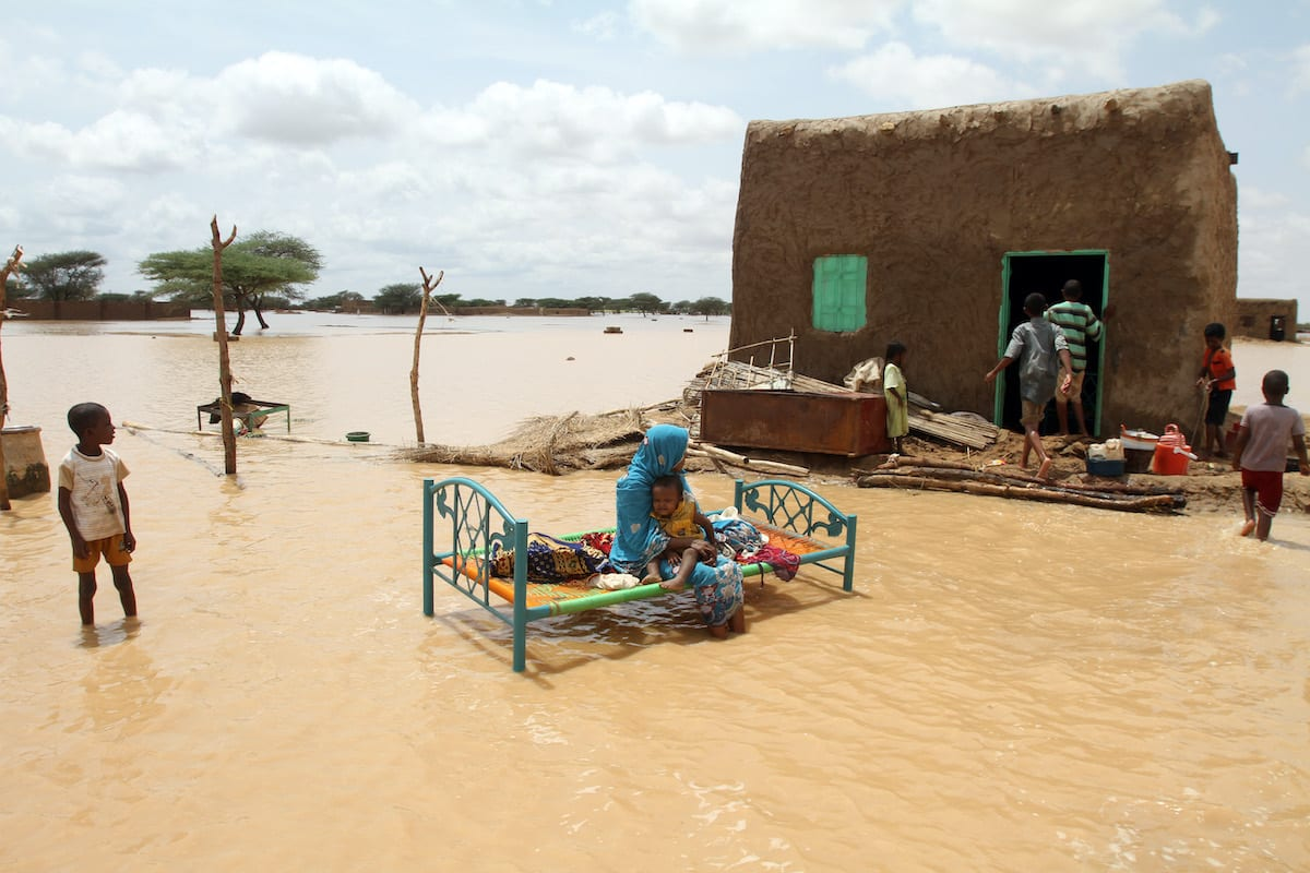 A Sudanese woman sits with her child next to her house in a flooded street on the outskirts of the capital Khartoum [ASHRAF SHAZLY/AFP via Getty Images]