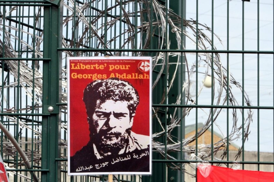 """A poster reading """"Freedom for Georges Abdallah"""" is placed near razor wire on the gate outside the prison in Lannemezan, southern France, on October 25, 2014 [LAURENT DARD/AFP via Getty Images]"""