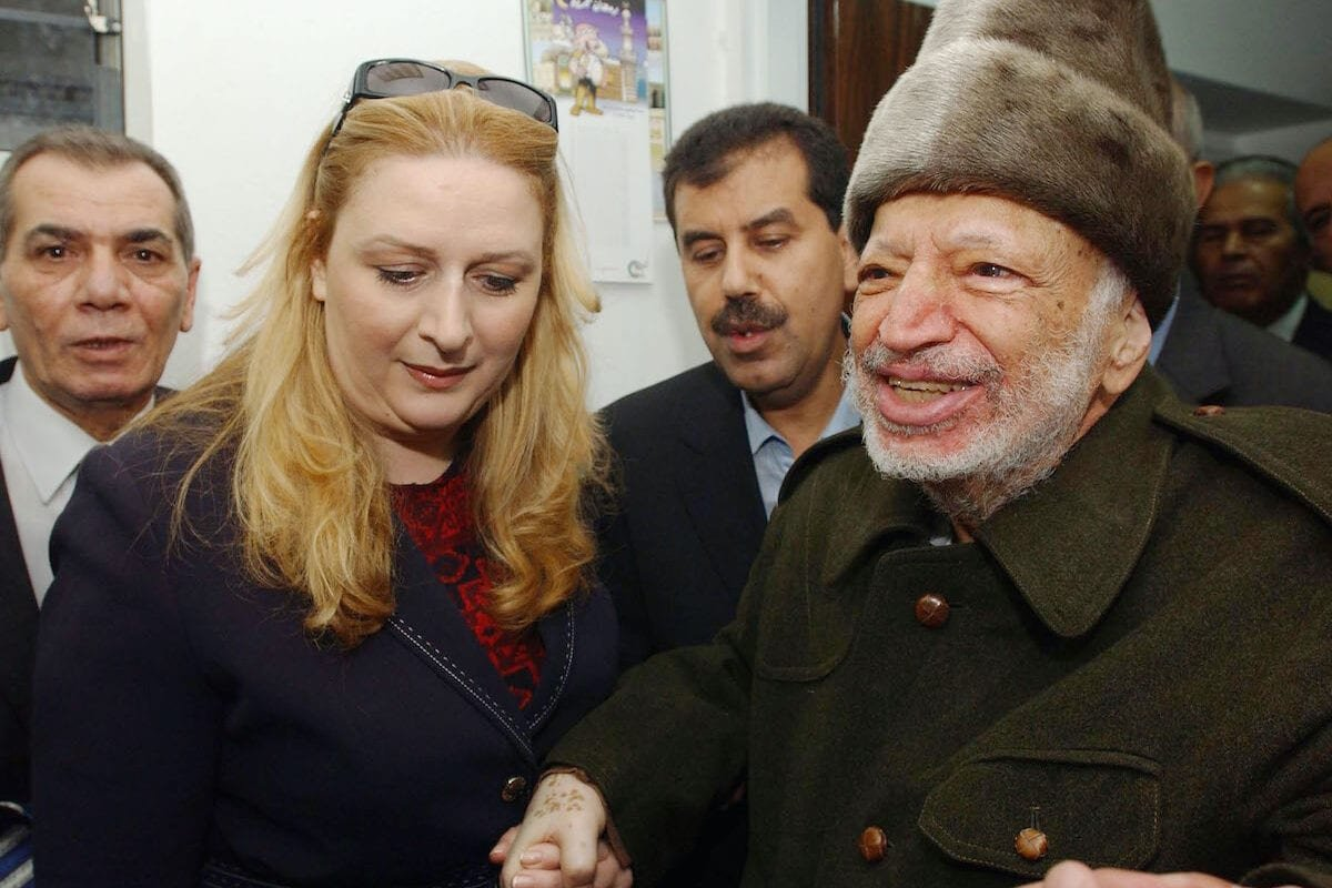 Palestinian leader Yasser Arafat is led out of his compound in the West Bank, by his wife Suha Arafat, to board a helicopter bound for France in order to seek medical attention for an unknown illness on 29 October 2004 in Ramallah, West Bank. [Hussein Hussein/PPO via Getty Images]