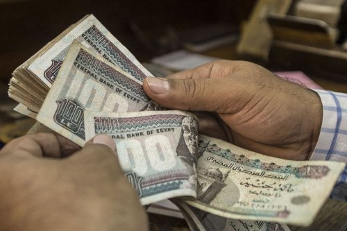 A man counts Egyptian pounds at currency exchange shop in downtown Cairo on 3 November 2016. [KHALED DESOUKI/AFP via Getty Images]