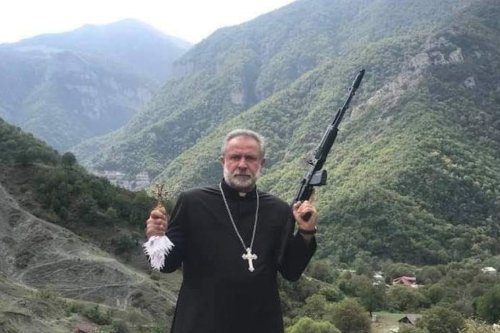 The image of a gun-wielding priest used by Armenia on Twitter as Azerbaijan declares state of war [armenia/Twitter]