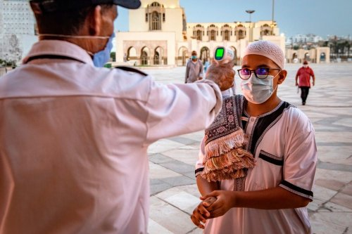 A mask-clad worker checks the body temperature of incoming Muslim worshippers in Morocco's Casablanca on 16 June 2020 [FADEL SENNA/AFP/Getty Images]