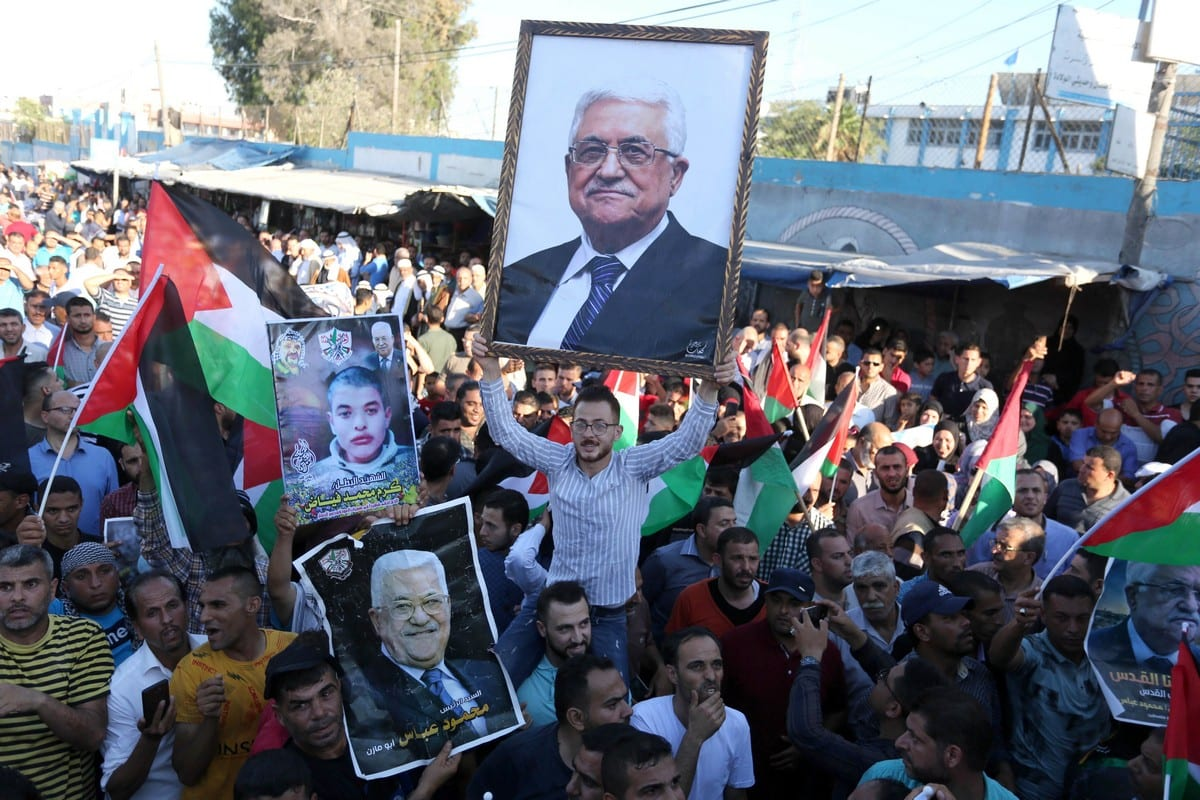 Palestinians waves national flags and hold posters of Palestinian President Mahmud Abbas during a demonstration against Israel's West Bank annexation plans in Khan Younis in the southern Gaza Strip, on July 2, 2020. [Ashraf Amra/Apaimages]