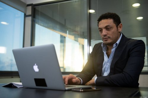 Egyptian self-exiled businessman Mohamed Ali looks at his laptop during an interview in an office near Barcelona on October 23, 2019. - Exiled Egyptian businessman, whose viral videos sparked rare small-scale protests in Egypt in September, says he is working with the opposition to topple President Abdel Fattah al-Sisi and calls for fresh demonstrations in the coming weeks. (Photo by Josep LAGO / AFP) (Photo by JOSEP LAGO/AFP via Getty Images)