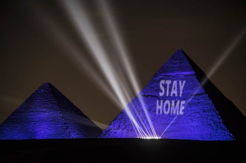 """A picture taken show the Great pyramids lighten-up with blue light and reading with a laser projection the message """"Stay Home"""" on the Giza plateau outside the Egyptian capital of Cairo, on the world heritage day, as the country fights against the spread of the COVID-19, on 18 April 2020 [KHALED DESOUKI/AFP via Getty Images]"""