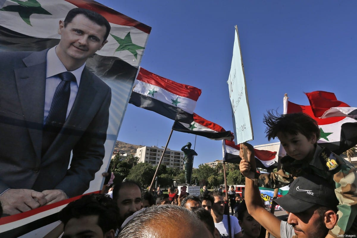 People wave Syrian national flags and pictures of President Bashar Al-Assad as they gather for a demonstration in support of Assad and against US sanctions on the country in Damascus on 11 June 2020 [LOUAI BESHARA/AFP/Getty Images]