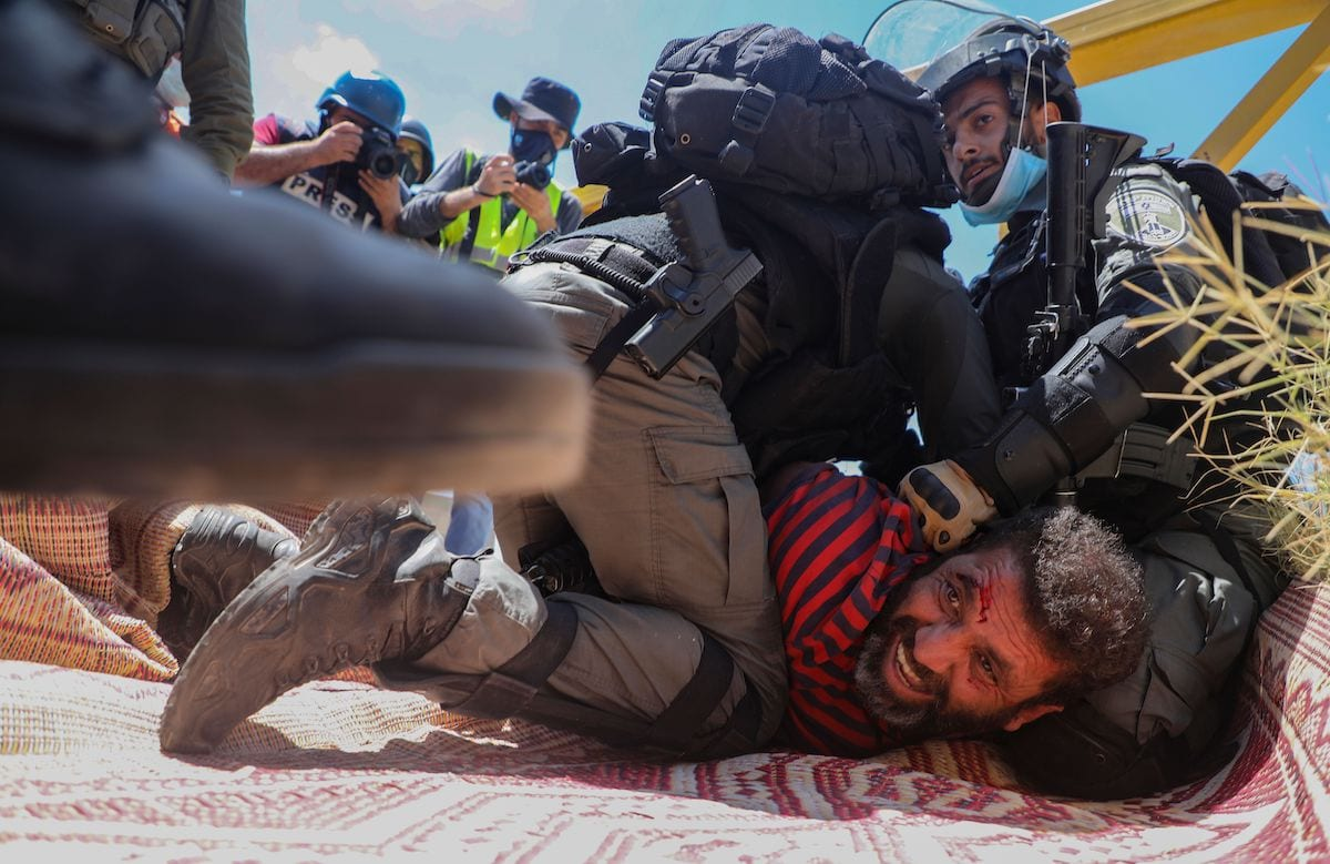 Members of the Israeli security forces arrest a Palestinian demonstrator during a rally to protest against Israel's plan to annex parts of the occupied West Bank, in the village of Haris, southwest of Nablus, on 21 August 2020. [JAAFAR ASHTIYEH/AFP via Getty Images]