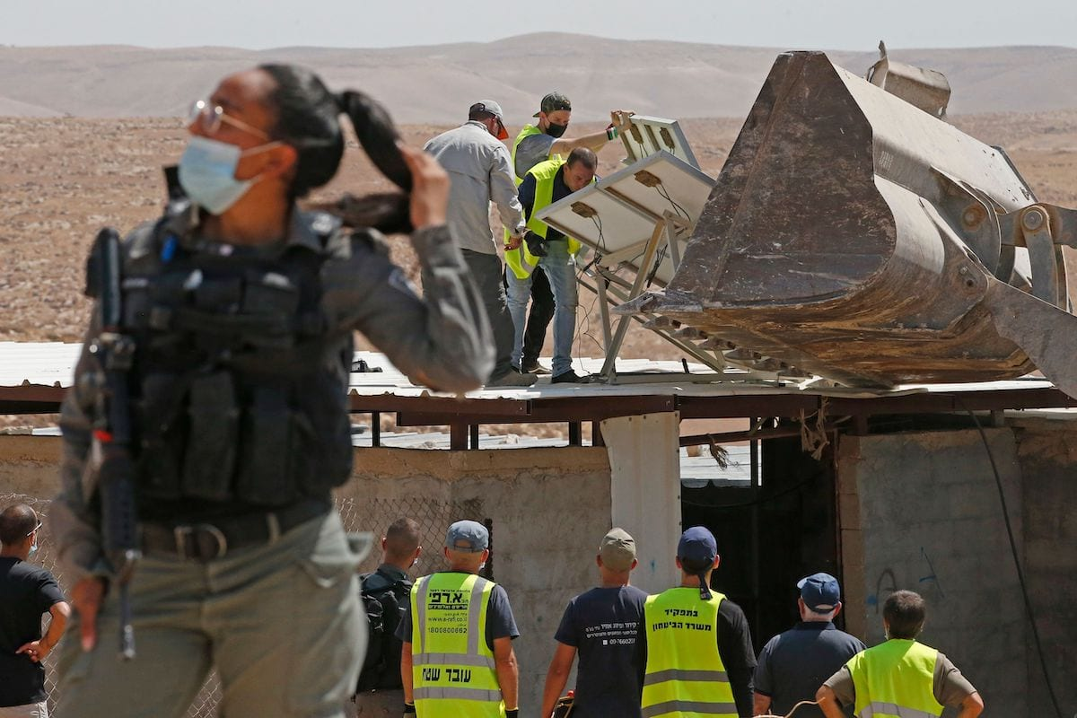 Men remove solar panels before Israeli authorities demolish the house and shack of a Palestinian family in the southern West Bank village of Khirbet Jinba on September 2, 2020, [HAZEM BADER/AFP via Getty Images]