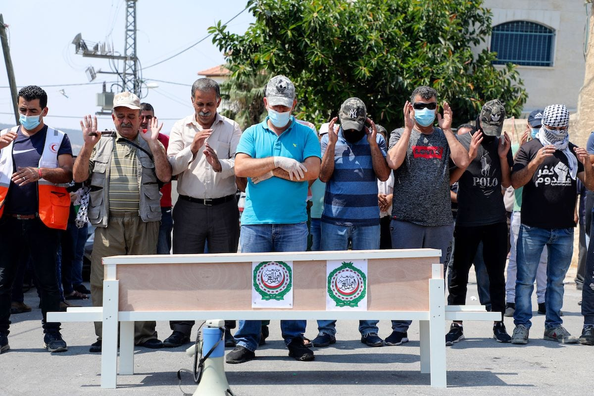 Palestinians pray next to a mock coffin, representing the Arab League, during a protest against the normalisation of ties between the Jewish state and the UAE, in the village of Kfar Qaddum in the Israeli-occupied West Bank, on 11 September 2020. [JAAFAR ASHTIYEH/AFP via Getty Images]