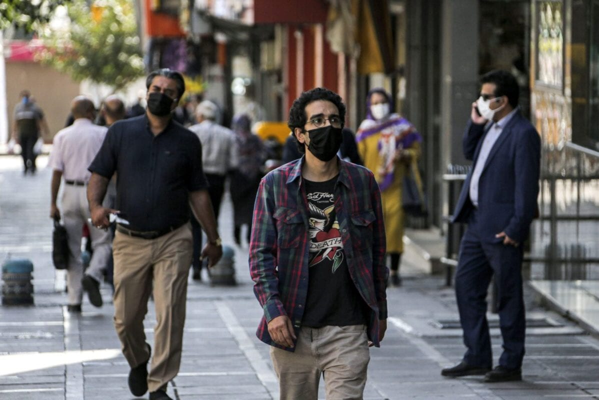 A man, mask-clad as a COVID-19 coronavirus pandemic precaution, walks past shops along a street in Iran's capital Tehran on September 27, 2020 [ATTA KENARE/AFP via Getty Images]