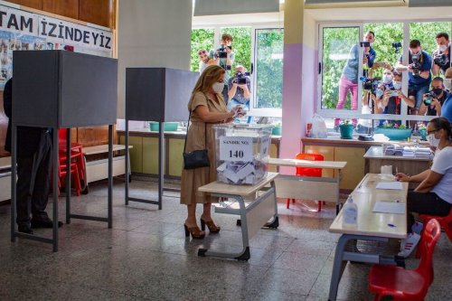 Sibel Tatar, the wife of Turkish-Cypriot Prime Minister of the self-proclaimed Turkish Republic of Northern Cyprus (TRNC) Ersin Tatar, casts her vote as the PM prepares his ballot at a polling station in the divided capital Nicosia, during the presidential election on 11 October 2020. [BIROL BEBEK/AFP via Getty Images]