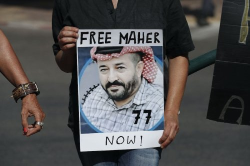 Israeli activists lift a placard bearing the picture of Palestinian administrative detainee Maher al-Akhras during a demonstration calling for his release on October 11, 2020 [AHMAD GHARABLI/AFP via Getty Images]
