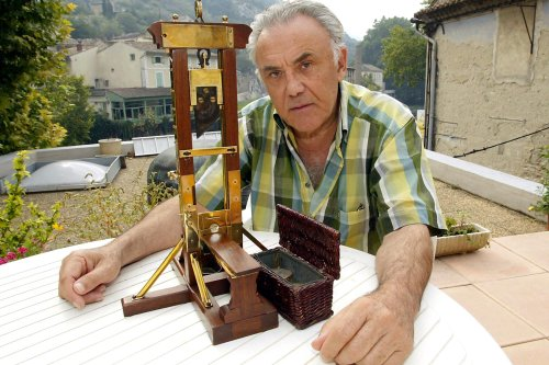 "TO GO WITH FRENCH AFP STORY : ""PEINES ET CHATIMENTS : LA COLLECTION D'UN BOURREAU AUX ENCHERES A PARIS "" A file picture taken on September 20, 2002, shows France's last surviving executioner in Algeria Fernand Meyssonnier showing the miniature replica of a guillotine in Fontaine-de-Vaucluse, southern France. He made this replica at the age of 15 as a present for his father who was chief executioner and inducted his son as an apprentice in 1947. AFP PHOTO GERARD JULIEN (Photo credit should read GERARD JULIEN/AFP via Getty Images)"