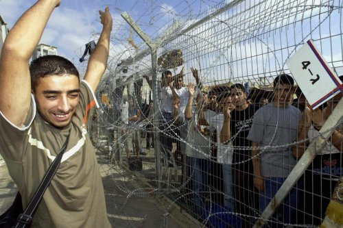 A detained Palestinian man waves to a group of other prisoners after his release from the Israeli Ktziot prison, in southern Israel 06 August 2003. Israel released dozens of Palestinian prisoners today to bolster a U.S.-backed peace plan. AFP PHOTO/Avi Ohayon/GPO **ISRAEL OUT** (Photo credit should read AVI OHAYON/AFP via Getty Images)