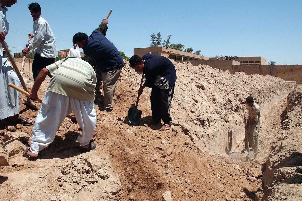 Iraqi men bury a body in a mass grave in a makeshift cemetary [Wathiq Khuzaie/Getty Image]