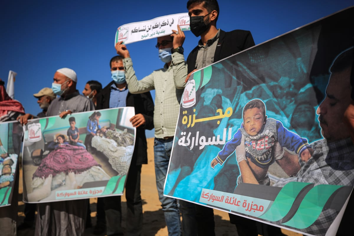Palestinians holding photos and banners gather to commemorate 9 members including 6 children of Sawarka family killed at their home during Israeli air raid on November 19, 2020 [Ali Jadallah/Anadolu Agency]