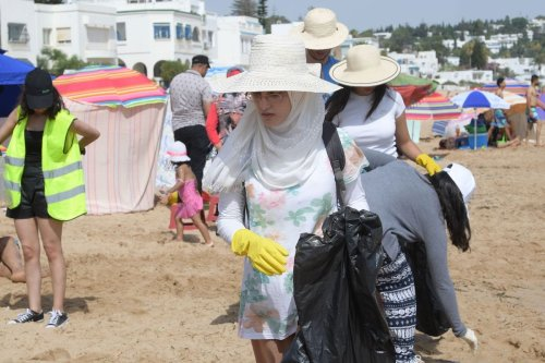 """Volunteers of """"CleanWalker"""" collect waste from a beach in the coastal town of Masra on July 14, 2019 near the capital Tunis [FETHI BELAID/AFP via Getty Images]"""