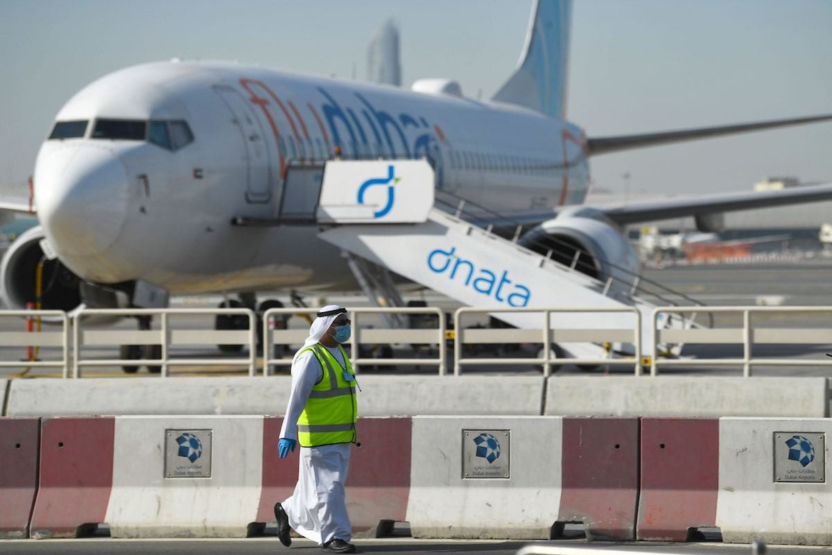 A mask-clad employee walks across a Flydubai aircraft on the tarmac of Dubai International Airport, on 6 April 2020. [KARIM SAHIB/AFP via Getty Images]