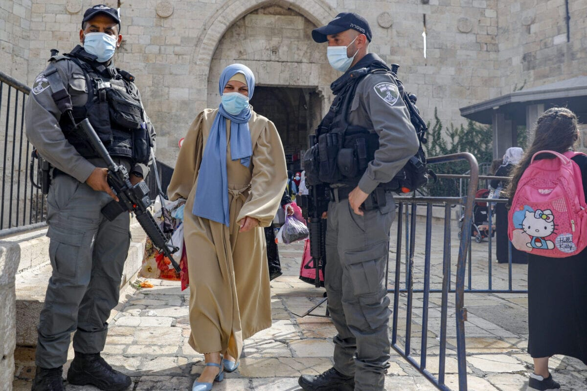 A Palestinian woman walks between members of the Israeli security forces in front of the Damascus Gate, in the Old City of Jerusalem on October 29, 2020 [AHMAD GHARABLI/AFP via Getty Images]