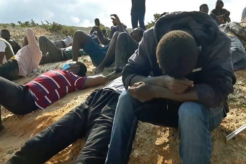 A video grab shows migrant survivors of a deadly shipwreck siting on a sandy beach on the coast of al-Khums, a port city 120 kilometres (75 miles) west of the Libyan capital Tripoli, on November 12, 2020. [AFP via Getty Images]